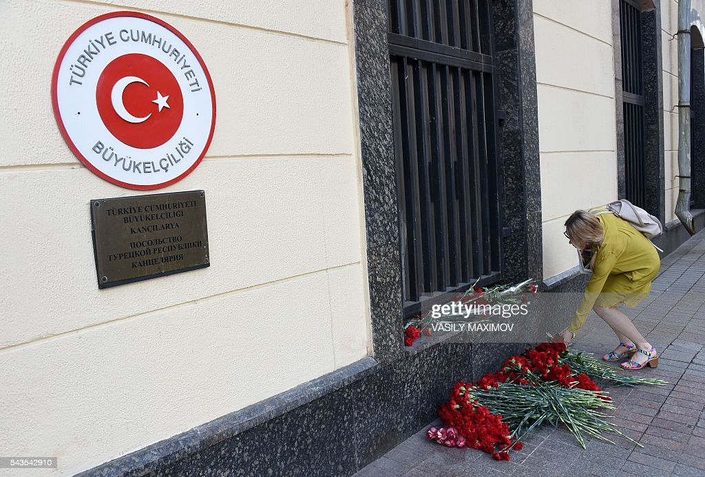 A woman lays flowers in front the Turkish embassy in Moscow on June 29, 2016 as people pay tribute to the victims of yesterday's suicide bombings at Istanbul's Ataturk airport. / AFP / VASILY