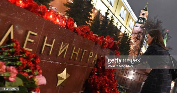 A woman lays flowers in memory of victims of the blast in the Saint Petersburg metro at a memorial stone reading Leningrad by the Kremlin wall in...