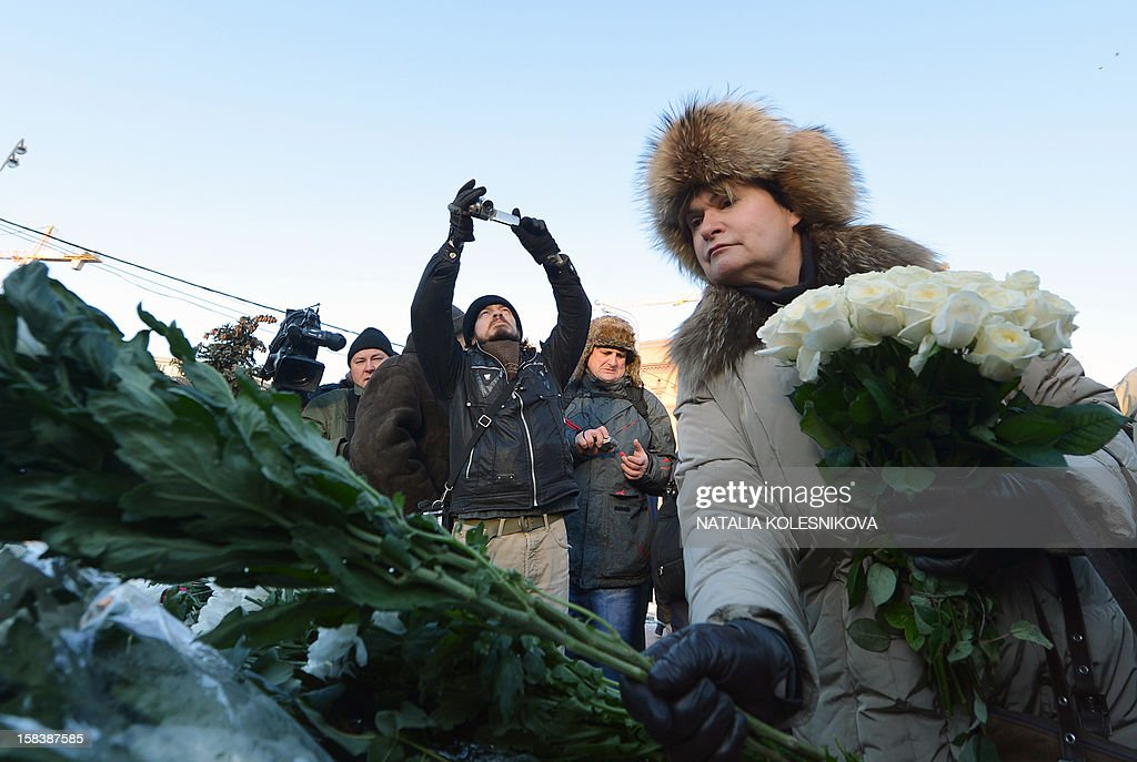 A woman lays flowers on a monument dedicated to victims of political repression during an opposition protest marking one year since the start of protests against Vladimir Putin, in Moscow, on December 15, 2012. Russia's opposition defied authorities who tried to ban the protest by holding a rally in central Moscow to mark one year since the start of protests against Vladimir Putin. The opposition Coordination Council led by charismatic lawyer Alexei Navalny urged Muscovites to defy city authorities by showing up at Lubyanka Square, the seat of the FSB security services, despite temperatures of minus 17 degrees C (one degree F) and warnings that unsanctioned rallies would be broken up.
