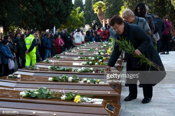 A woman lays flowers on the bars of the migrant women in the Monumental Cemetery of Salerno on November 17 2017 in Salerno Italy A funeral was held...