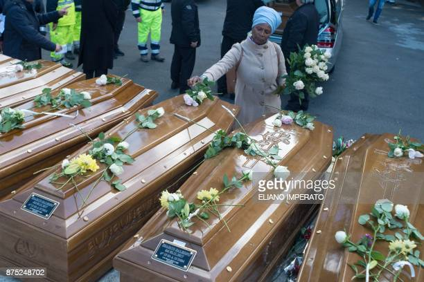 A woman lays flowers on the coffins of 26 teenage migrant girls found dead in the Mediterranean in early November during the inter religious funeral...