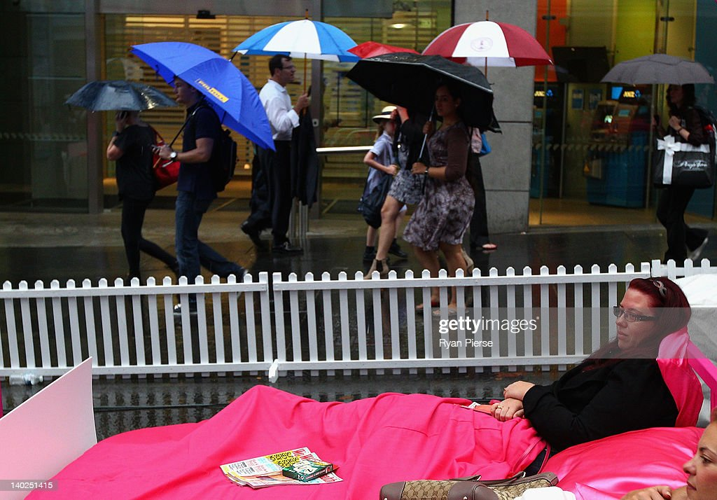 A woman lays in bed as morning commuters make their way to work during the The World's Biggest Breakfast in Bed Guinness World Record Attempt at Martin Place on March 2, 2012 in Sydney, Australia.