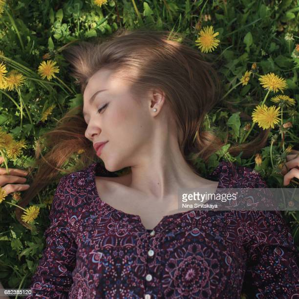 Woman lays in grass with dandelion flowers