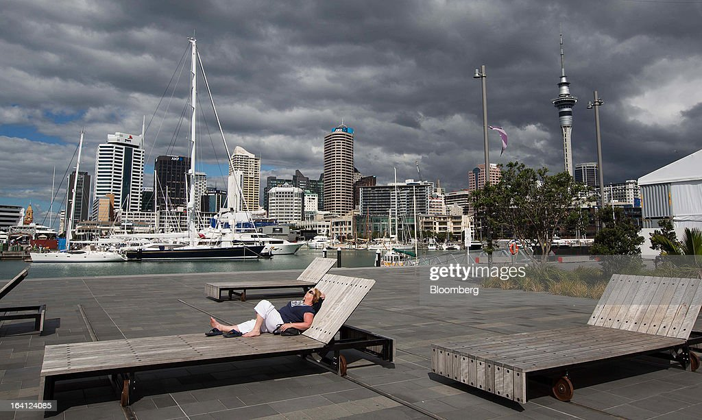A woman lays on a bench in the sun in front of the central business district in Auckland, New Zealand, on Wednesday, March 20, 2013. The New Zealand dollar, nicknamed the kiwi, fell against most major peers as the government said the country's most widespread drought in at least 30 years reduces pressure to raise interest rates. Photographer: Brendon O'Hagan/Bloomberg via Getty Images
