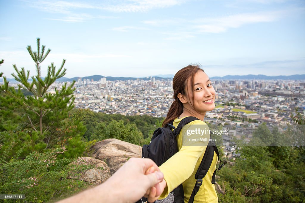 A woman leading a man to a viewpoint