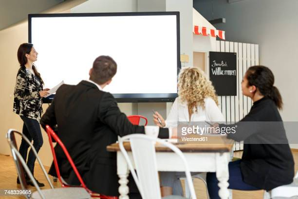 Woman leading presentation in office at large screen