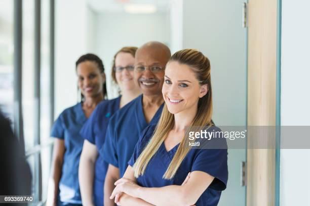 Mujer liderando equipo de profesionales médicos y multiétnicos