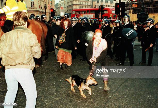 A woman leads her dog away from a line of policemen in riot gear after a protest against the socalled Poll Tax erupted into a riot affecting...