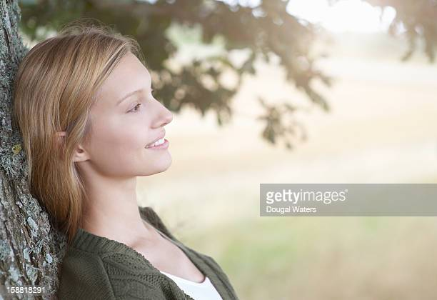 Woman leaning against a tree in the countryside
