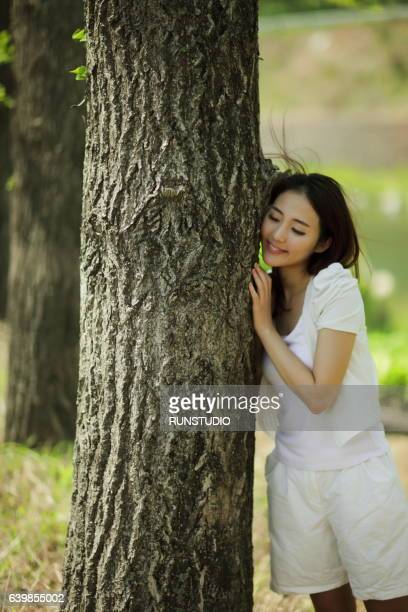 woman leaning against a tree outdoors