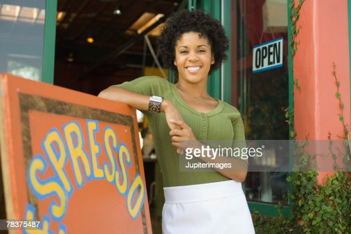 Woman leaning against coffee shop sign : Foto de stock