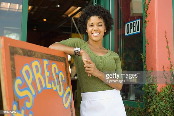 Woman leaning against coffee shop sign