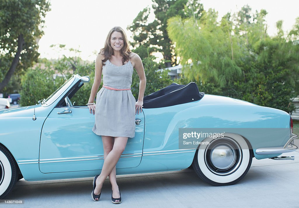 Woman leaning against convertible : Stock Photo
