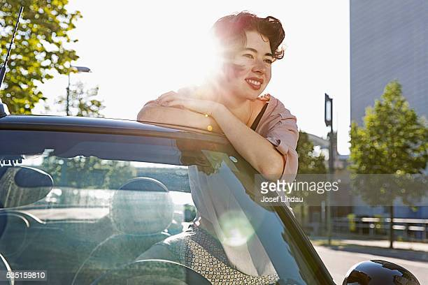 Woman leaning against convertible