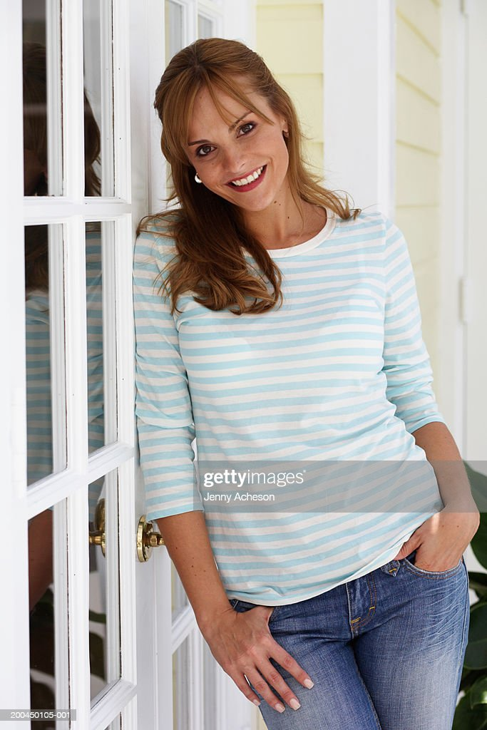 Woman leaning against glass door, smiling, portrait : Stock Photo