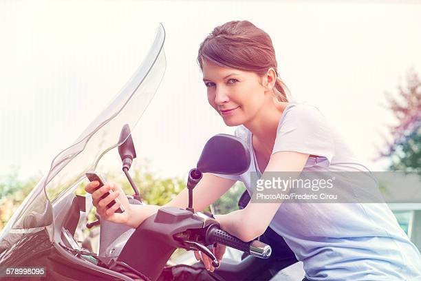 Woman leaning against motorcycle, using smartphone