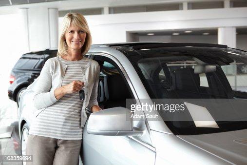 Woman leaning against new car in showroom : Foto de stock
