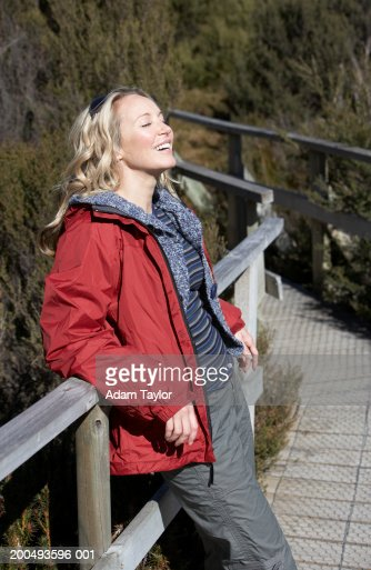 Woman leaning against railing, laughing : Stock Photo