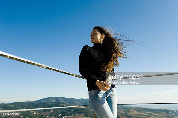 Woman leaning against railing, looking at view