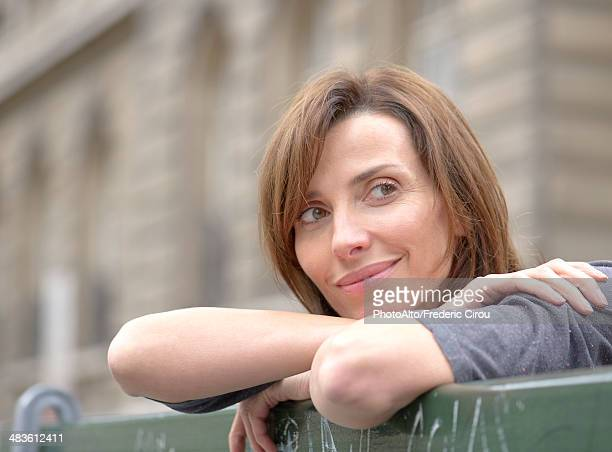Woman leaning against railing, looking away in thought, portrait