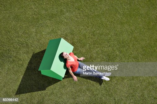 Woman leaning against small model house