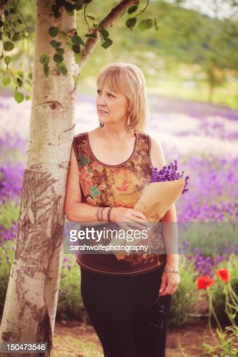 Woman leaning against tree in field of lavende : Foto de stock