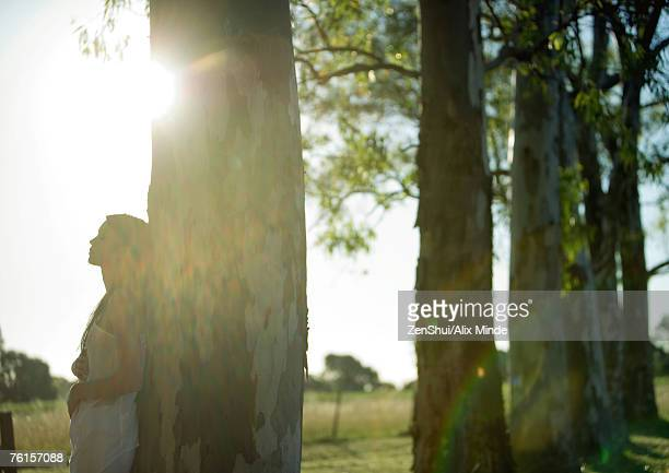 Woman leaning against tree, sun in background
