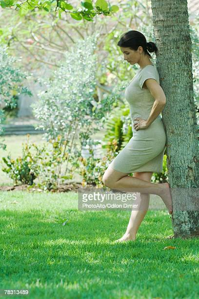 Woman leaning against tree trunk, side view, full length