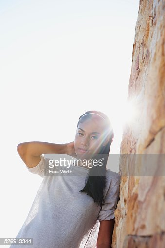 Woman leaning against wall : Stockfoto
