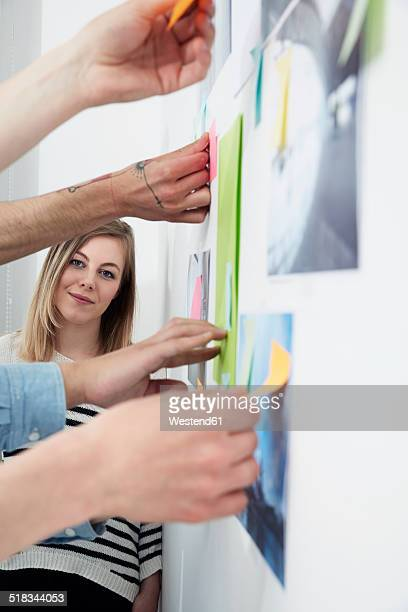 Woman leaning against wall with adhesive notes