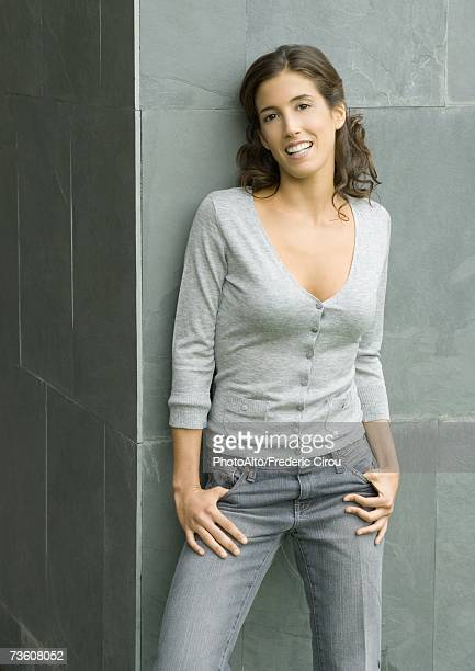 Woman leaning against wall with thumbs in pockets, portrait