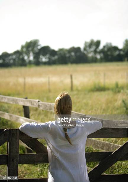 Woman leaning against wooden fence, rear view