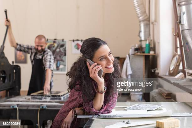 Woman leaning and using smart phone in printing house