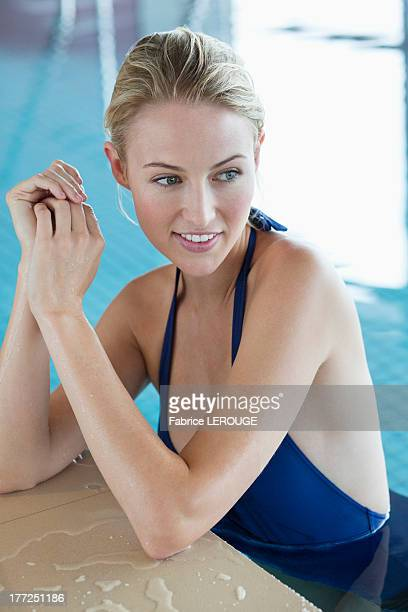 Woman leaning at the edge of a swimming pool