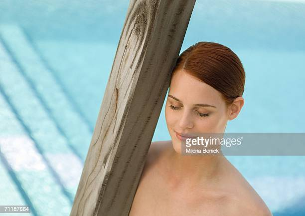 Woman leaning head against wooden pole, pool in background