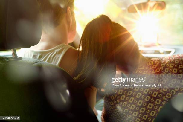 Woman leaning head on shoulder of man driving sunny car