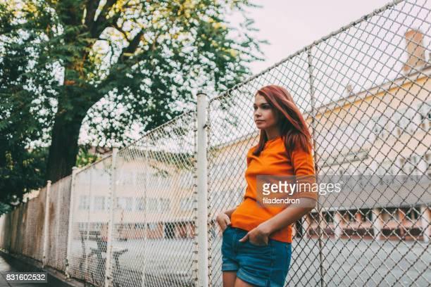 Frau, stützte sich auf einen Zaun im freien