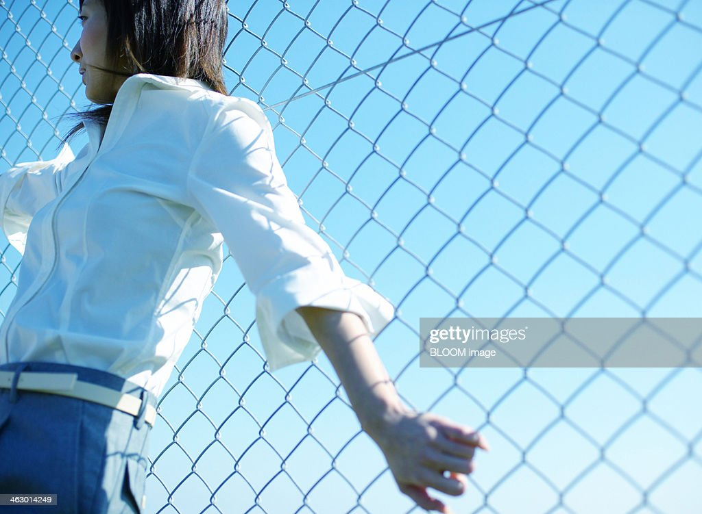 Woman Leaning On A Fence