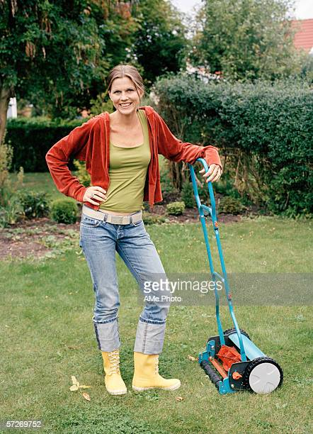 A woman leaning on a lawn mower in a garden.