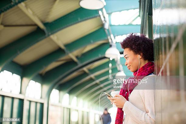 Woman leaning on a wall waiting for the train