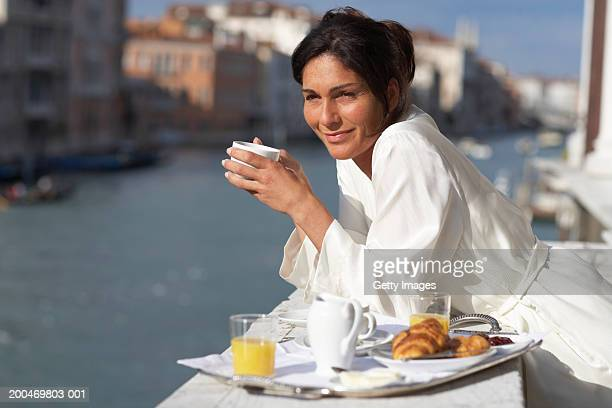 Woman leaning on balcony beside breakfast tray, smiling