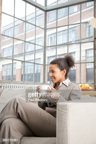 Woman leaning on couch drinking coffee : Stock Photo