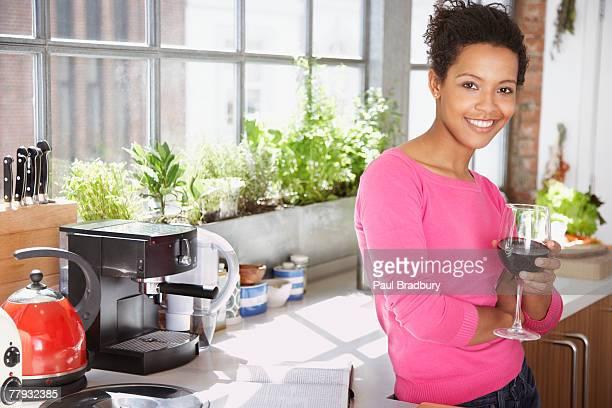 Frau schiefen auf der Theke in der Küche mit einem Glas