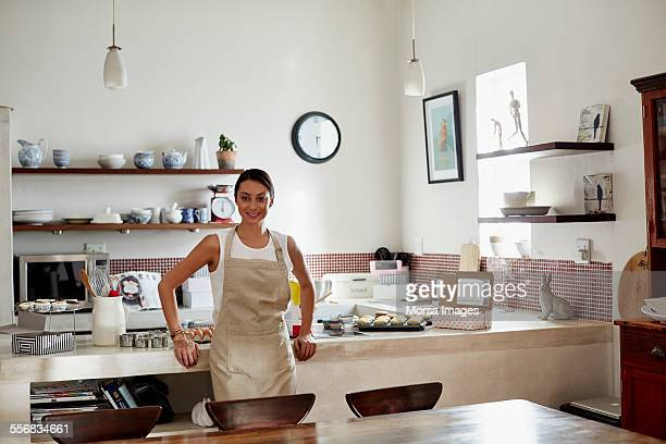 Woman leaning on counter while preparing cupcakes