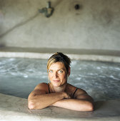Woman leaning on edge of whirlpool, portrait