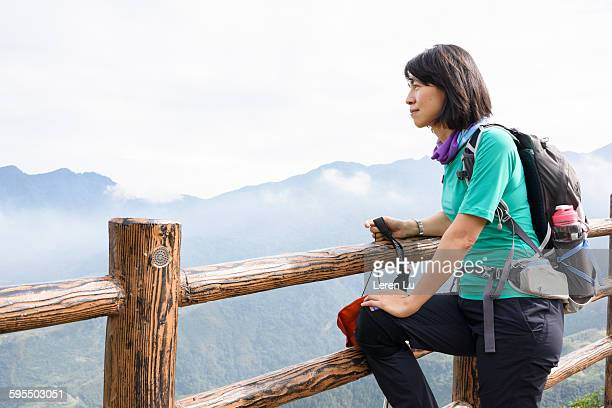 Woman leaning on fence on top of hill