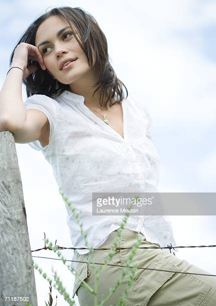 Woman leaning on fence post