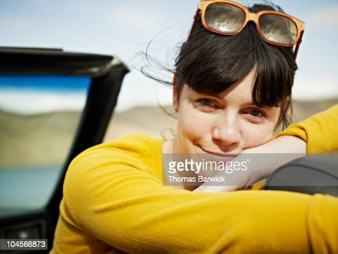 Woman leaning on headrest in convertible : Stock Photo