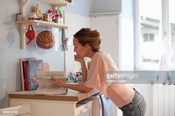 woman leaning on kitchen counter, reading cookbook