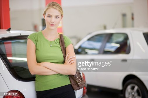 Woman leaning on new car in showroom